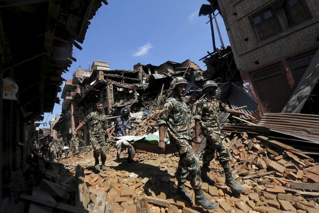 Nepalese army personnel carry a dead body recovered from the rubble of a damaged house following Saturday's earthquake, in Bhaktapur, Nepal April 27, 2015. (Photo by Adnan Abidi/Reuters)