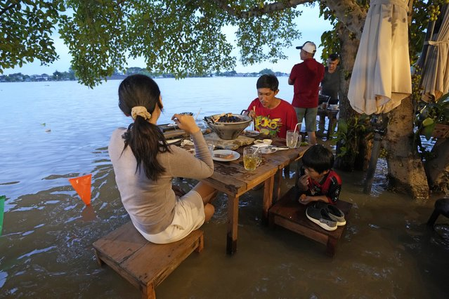 Customers of the riverside Chaopraya Antique Café enjoy themselves despite the extraordinary high water levels in the Chao Phraya River in Nonthaburi, near Bangkok, Thailand, Thursday, October 7, 2021. (Photo by Sakchai Lalit/AP Photo)