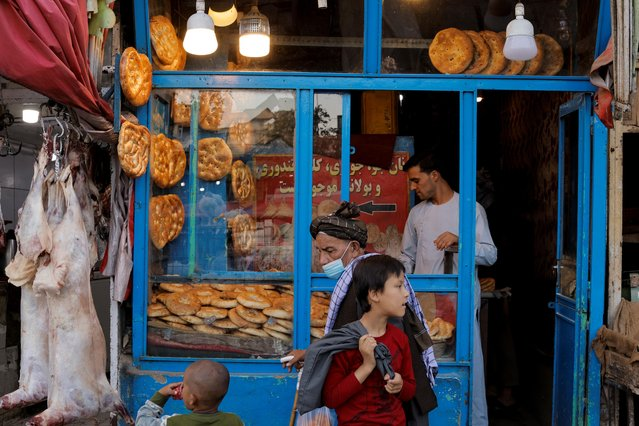 People walk in front of a bakery in Kabul, Afghanistan, October 4, 2021. (Photo by Jorge Silva/Reuters)