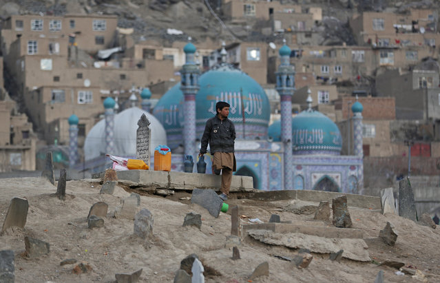 Haseeb, 13, an Afghan boy waits for customers to sell water in Kart-e Sakhi cemetery in Kabul, Afghanistan, Wednesday, Jan. 29, 2014. Children sell water in cemeteries for visitors to pour it on their relatives' graveyards. (Photo by Massoud Hossaini/AP Photo)