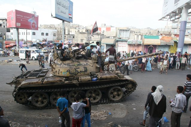 Pro-government fighters ride on a tank in the Bir Basha neighbourhood after they took the area from Houthi fighters in Yemen's southwestern city of Taiz March 11, 2016. (Photo by Anees Mahyoub/Reuters)