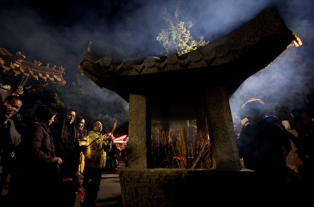 People burn incense sticks and pray to mark the Lunar New Year at the International Buddhist Temple in Richmond, British Columbia. Thousands of people gathered at the temple to celebrate the beginning of the new year, which in 2014 is the Year of the Horse according to the Chinese zodiac. (Photo by Darryl Dyck/The Canadian Press)