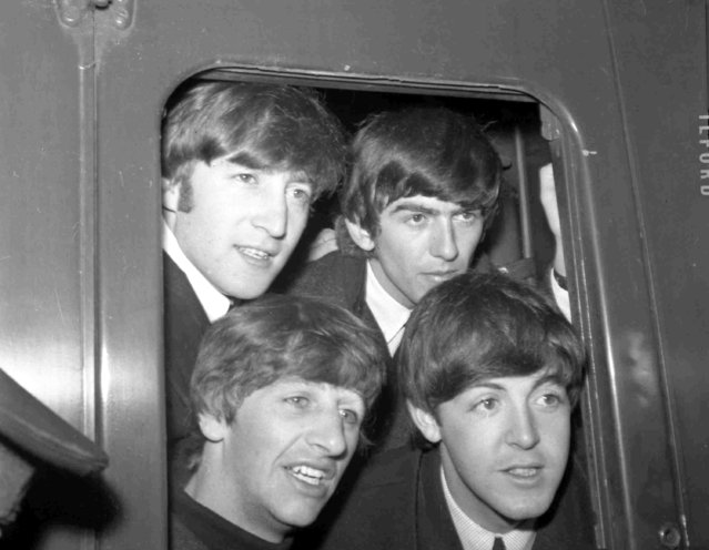 Britain's pop group The Beatles pose in a carriage window of train before they left Paddington Station, London, March 2, 1964, to start filming their first feature film. Top left is John Lennon, with George Harrison next to him, and Ringo Starr, bottom left, with Paul McCartney next to him. (Photo by Bob Dear/AP Photo)
