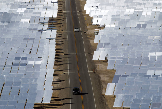 Vehicles drive through field of heliostats (mirrors that track the sun and reflect the sunlight onto a central receiving point) at the Ivanpah Solar Electric Generating System in the Mojave Desert near the California-Nevada border February 13, 2014. The project, a partnership of NRG, BrightSource, Google and Bechtel, is the world's largest solar thermal facility and uses 347,000 sun-facing mirrors to produce 392 Megawatts of electricity, enough energy to power more than 140,000 homes. (Photo by Steve Marcus/Reuters)