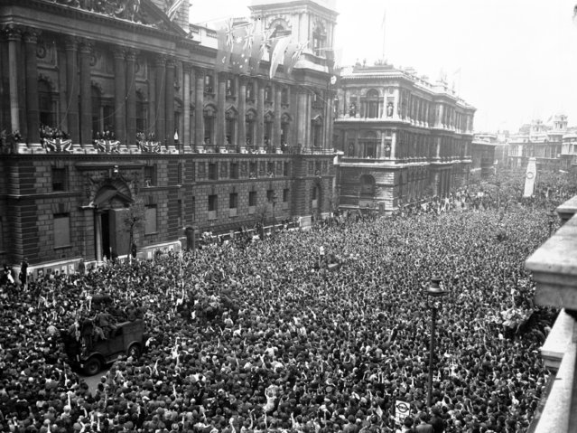 Crowds of civilians, British and Allied troops wave and cheer as Winston Churchill, second balcony from left, and members of the cabinet appear, to celebrate the end of the war in Europe, in Whitehall, London, May 8, 1945. (Photo by AP Photo)