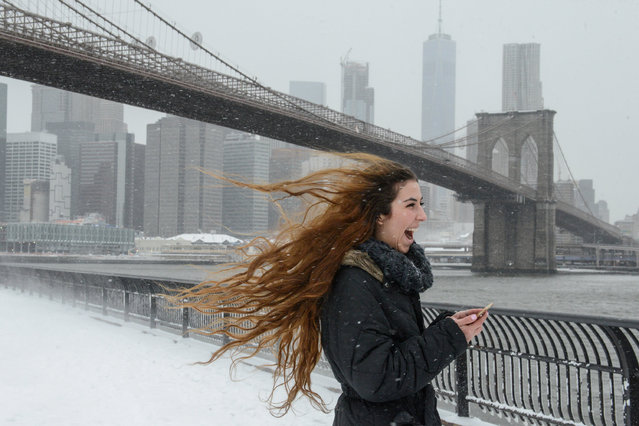 Lenessa Age laughs as her hair is blown by a gust of wind in front of the Brooklyn Bridge during winter storm Niko in the Brooklyn borough of New York City, U.S. February 9, 2017. (Photo by Stephanie Keith/Reuters)