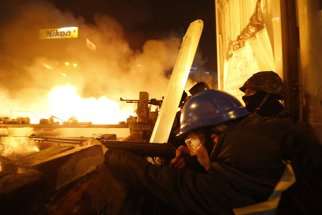 Anti-government protesters aim their weapons during clashes with riot police at Independence Square in Kiev February 18, 2014. (Photo by Vasily Fedosenko/Reuters)