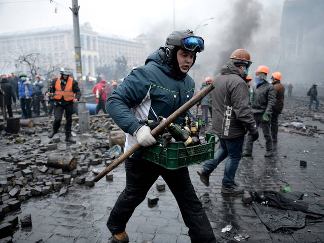 Protester carries bottles during the clashes with police in Independence square in Kiev, on February 20, 2014. (Photo by Jeff J. Mitchell/Getty Images)