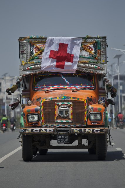 A Nepalese truck with a Red Cross flag drives through the streets of Kathmandu, Nepal, Sunday, May 3, 2015. With monsoon rains expected in a few weeks, Nepal has pleaded with donors to send tents and temporary shelters for earthquake victims who have been living in the open for more than a week, with their homes damaged by the April 25 quake. (Photo by Bernat Amangue/AP Photo)