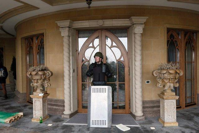 A protester guards the entrance to Ukrainian President Yanukovych's countryside residence in Mezhyhirya, on February 22, 2014. (Photo by Efrem Lukatsky/AP Photo)