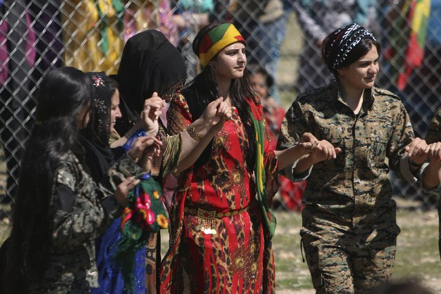 Kurdish female fighters from the People's Protection Units (YPG) and women wearing traditional dresses, dance as they celebrate the spring festival of Newroz in the northeast Syrian Kurdish city of Qamishli, Syria March 21, 2016. (Photo by Rodi Said/Reuters)