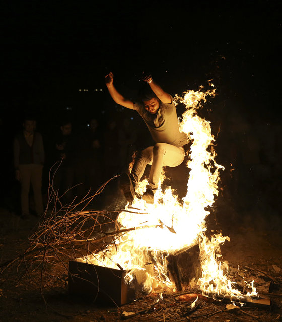 An Iranian man jumps over a bonfire during Chaharshanbe Souri, or Wednesday Feast, an ancient Festival of Fire, on the eve of the last Wednesday of the solar Persian year, in Tehran, Iran, Tuesday, March 17, 2015. (Photo by Vahid Salemi/AP Photo)