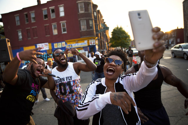 Local rappers from right, Kova, Bilal and Spence sing on a street corner near the scene of some of Monday's rioting following Freddie Gray's funeral, Sunday, May 3, 2015, in Baltimore. (Photo by David Goldman/AP Photo)