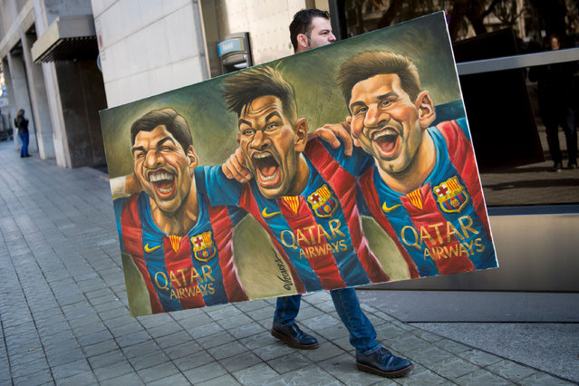 "A man carries a painting representing Spanish Barcelona's Uruguayan forward Luis Suarez (L), Barcelona's Brazilian forward Neymar and Barcelona's Argentinian forward Lionel Messi (R) painted by Spanish cartoonist Vizcarra to the presentation of the 12th edition of the book entitled ""Relats solidaris de l'esport"" (Stories of solidarity in sport) in Barcelona on February 17, 2017. (Photo by Josep Lago/AFP Photo)"