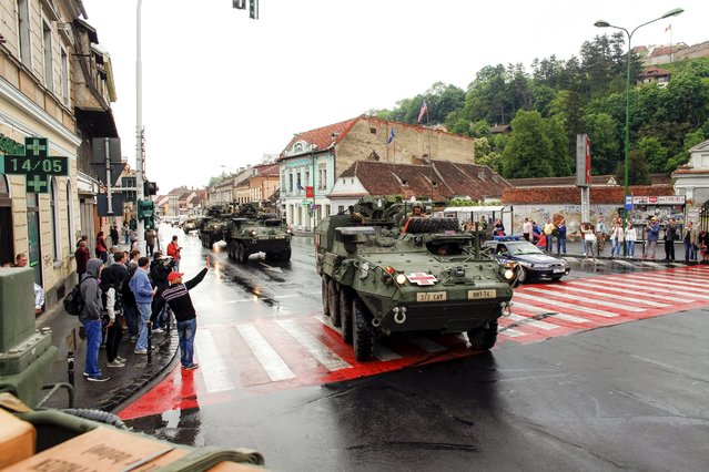 People wave hands as a convoy of U.S. and Romanian military vehicles passes Brasov, Romania May 14, 2015. Troops assigned to the 2nd Squadron, 2nd Cavalry Regiment of the U.S army are in Romania to participate in Operation Atlantic Resolve-South, an international military exercise. (Photo by Ovidiu Micsik/Reuters/Inquam Photos)