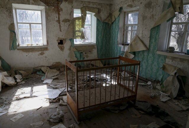 A baby cot is seen in a house in the abandoned village of Zalesye near the Chernobyl nuclear power plant in Ukraine on March 28, 2016. (Photo by Gleb Garanich/Reuters)