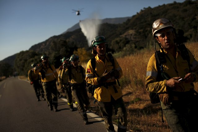 A helicopter drops water over a wildfire as firefighters walk along a road after extinguishing it in Benahavis, southern Spain, May 19, 2015. (Photo by Jon Nazca/Reuters)