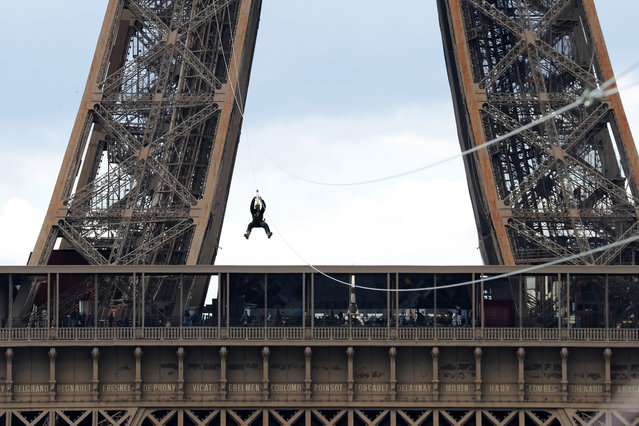 A person rides on a zip-line descending from the second floor of the Eiffel Tower on May 28, 2019 in Paris. The 800 meter crossing takes one minute at a speed of 90km/h. The zip-line will be opened from May 29 to June 2, 2019. (Photo by Francois Guillot/AFP Photo)