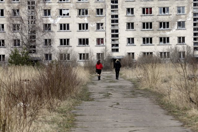 People walk to the abandoned apartment house in the ghost town of a former Soviet military radar station near Skrunda, Latvia, April 9, 2016. (Photo by Ints Kalnins/Reuters)