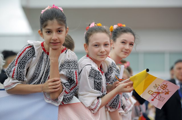 Young girls wearing traditional Romanian clothes and holding a Vatican flag waits for the arrival of Pope Francis from Rome, at Henri Coanda International Airport in Otopeni, near Bucharest, Romania, Friday, May 31, 2019. Pope Francis is heading to Romania for a three-day, cross-country pilgrimage that in many ways is completing the 1999 trip by St. John Paul II that marked the first-ever papal visit to a majority Orthodox country. (Photo by Vadim Ghirda/AP Photo)