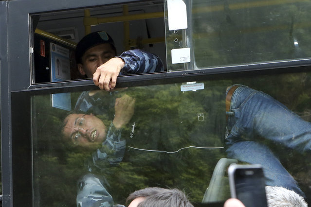 A detained demonstrator shouts, seen through a police bus, during an anti-government protest during the presidential elections in Nur-Sultan, the capital city of Kazakhstan, Sunday, June 9, 2019. Voters in Kazakhstan are choosing a successor to the president who had led the Central Asian country since independence from the Soviet Union, with a longtime loyalist expected to win easily. (Photo by Alexei Filippov/AP Photo)