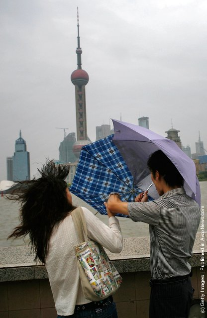 A woman tries to hold her umbrella in big wind triggered by typhoon Wipha at the Bund
