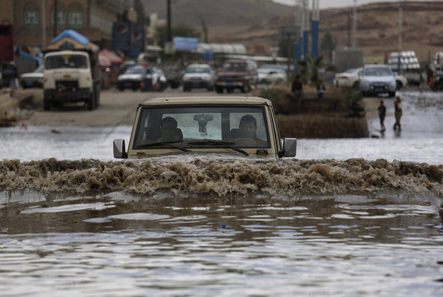 A motorist drives in floodwaters after a heavy rain in Sanaa, Yemen, Wednesday, April 13, 2016. (Photo by Hani Mohammed/AP Photo)