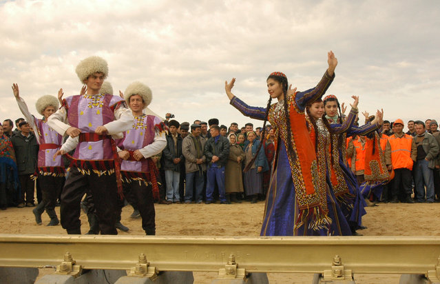 Folklore dancers perform in front of workers during a laying-down ceremony of a golden link of the Ashgabat-Karakum-Dashoguz railroad near Darvaza in the Karakum Desert north of the capital Ashgabat February 10, 2006. (Photo by Olukbek Tagtabayev/Reuters)
