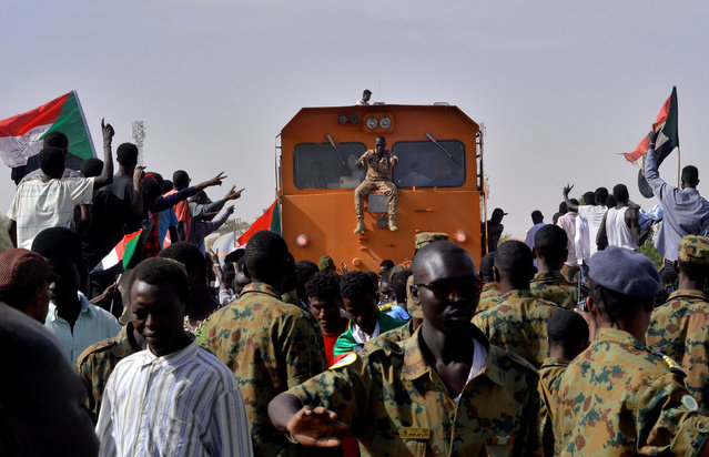 Sudanese military and demonstrators attending a sit-in block a train from passing through, during a protest outside the Defence Ministry in Khartoum, Sudan on April 14, 2019. (Photo by Reuters/Stringer)