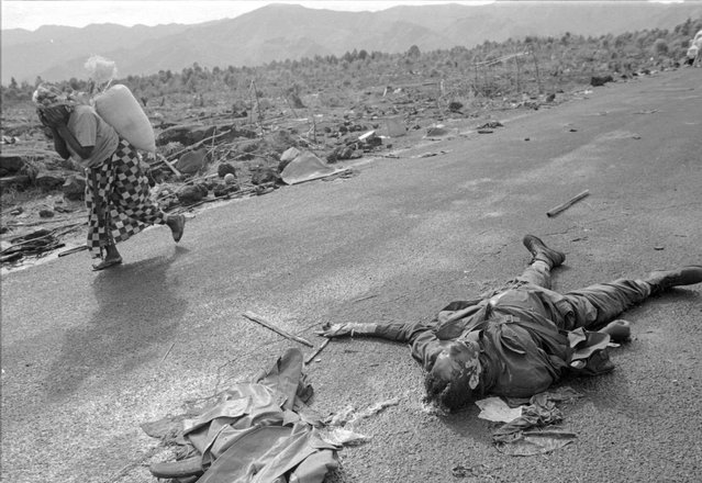 A Rwandan refugee passes by the body of a Hutu militia soldier killed during fighting with Zairian rebels; 1996. (Photo by Carol Guzy/The Washington Post)