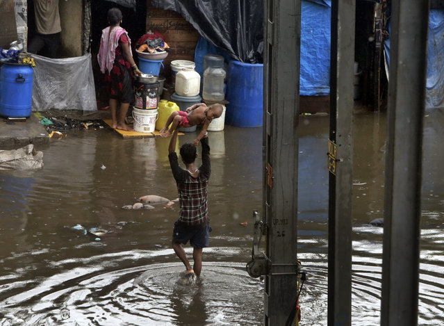 A man holds a child high above his head as he wades through a waterlogged street following heavy rains in Mumbai, India, Tuesday, July 2, 2019. Heavy monsoon rains in western India caused at least three walls to collapse onto huts and city shanties, killing more than two dozen people and injuring dozens of others, officials said Tuesday, as forecasters warned of more rains. (Photo by Rajanish Kakade/AP Photo)
