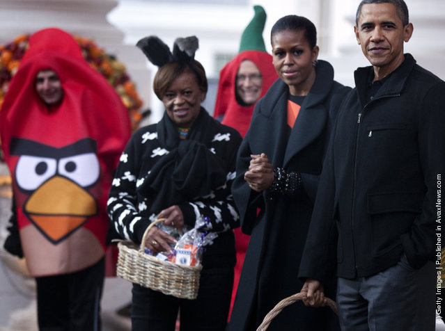 President Barack Obama waits with first lady Michelle Obama and her mother Marian Robinson to greet trick or treaters at the White House