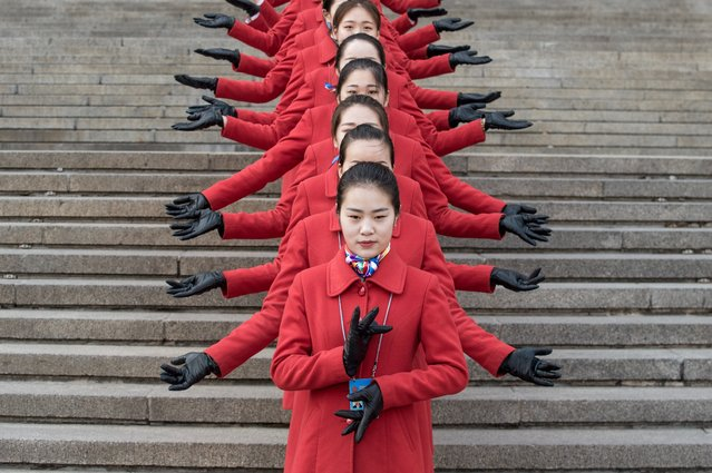Hostesses pose for a picture during the opening session of the Chinese People's Political Consultative Conference (CPPCC) in the Great Hall of the People in Beijing on March 3, 2017. The CPPCC plays a largely symbolic role, with members meeting once a year to discuss social and economic policies, among them wealthy business leaders and members of powerful political families. (Photo by Fred Dufour/AFP Photo)