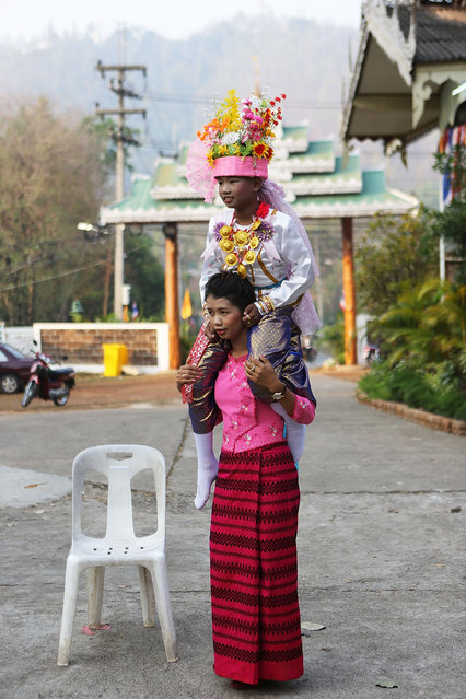 A Tai Yai boy poses for a portrait on the shoulders of a relative during Poy Sang Long on April 7, 2014 in Mae Hong Son, Thailand. Poy Sang Long is a Buddhist novice ordination ceremony of the Shan people or Tai Yai, an ethnic group of Shan State in Myanmar and northern Thailand. Young boys aged between 7 and 14 are ordained as novices to learn the Buddhist doctrines. It's believed that they will gain merit for their parents by ordaining. (Photo by Taylor Weidman/Getty Images)