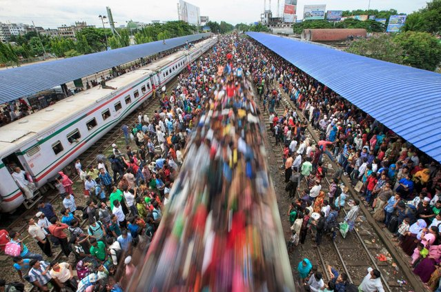 A train passes under the photographer turning the people on it's roof blurred as it moves passed. A busy rush hour sees thousands of commuters climbing on board a train – as well as holding onto its sides and sitting on the roof before it speeds off. Men, women and children climb and are pulled up onto the roof of the train, which is around 12ft (3.6m) high, as they try to find themselves a space. With no seats available inside, many commuters decide to take the risk and choose a rooftop view for their journey out of Dhaka city, in Bangladesh. (Photo by Yousuf Tushar/Solent News & Photo Agency)