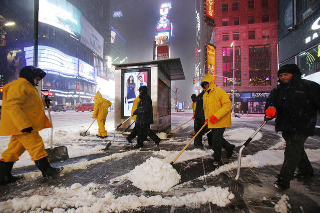 A crew of snow shovelers work as a snowstorm sweeps through Times Square, Tuesday, March 14, 2017, in New York. (Photo by Mark Lennihan/AP Photo)