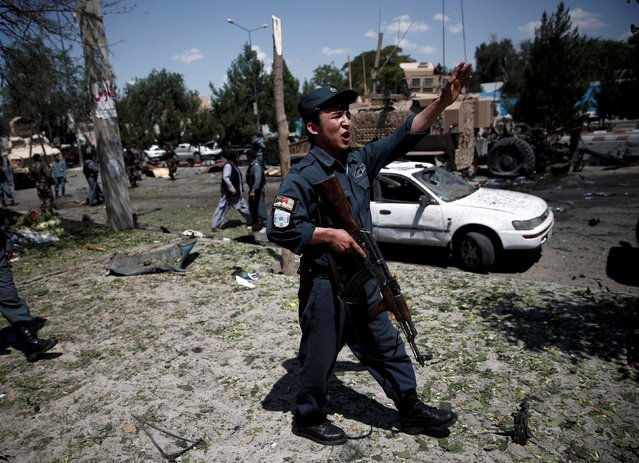 An Afghan policeman reacts at the site of a suicide bomb attack in Kabul, Afghanistan June 30, 2015. (Photo by Ahmad Masood/Reuters)