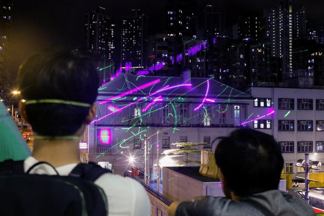 Anti-extradition bill protesters watch as demonstrators point laser pens at the police station in Sham Shui Po in Hong Kong, China, August 14, 2019. (Photo by Thomas Peter/Reuters)