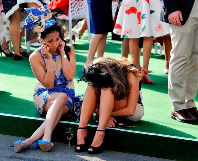 After a busy day of racing – a couple of friends give their feet a rest during the Grand National Festival at Aintree Racecourse on April 7, 2017 in Liverpool, England. (Photo by South West News Service)