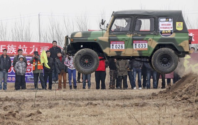 A car jumps over a sand dune as spectators stand by during a cross country event in Wudi county, Shandong province, December 2, 2012. Picture taken December 2, 2012. (Photo by Reuters/China Daily)