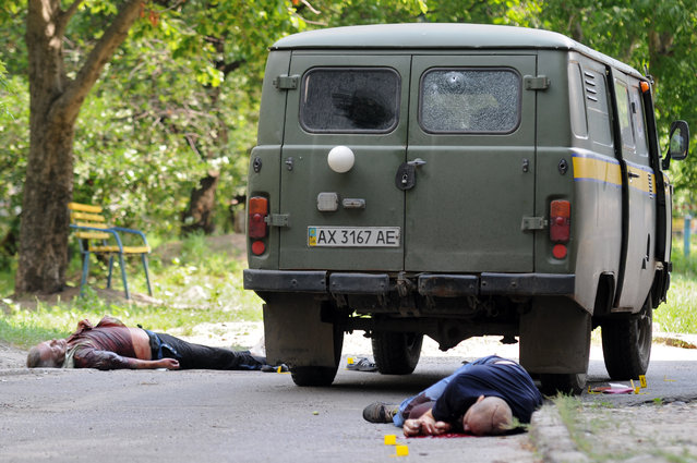 Dead bodies of  post collectors lies near  their vehicle after an attack in Kharkiv, Ukraine, Friday 10, 2015. The robber who shot three collectors  took control of 2.3 million hryvnias, approximately one million US dollars. (Photo by Andrei Markov/AP Photo)