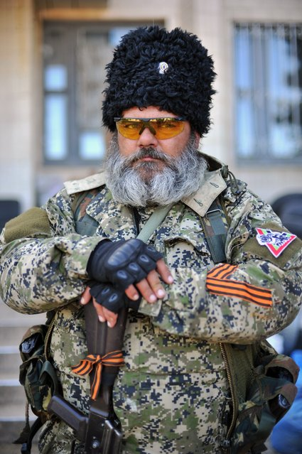 A pro-Russian militants holds a Kalashnikov as he guards a barricade outside the city hall in downtown Kramatorsk, eastern Ukraine, on May 6, 2014, a day after heavy fightings between pro-Russian militiants and Ukranian troops killed at least 34 people near the eastern Ukranian city of Slavyansk. The death toll from a military offensive in a flashpoint town in east Ukraine rose to at least 34, officials said on May 6, amid fresh warnings of civil war and the shutdown of a major airport in the region. (Photo by Genya Savilov/AFP Photo)