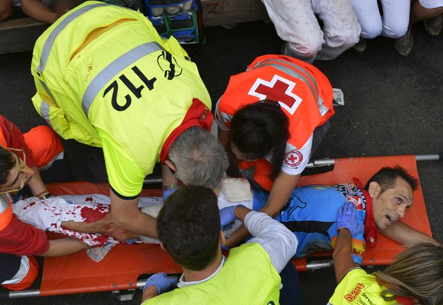 A runner is attended by medical services after being gored  by a Jose Escolar fighting bull at Telefonica corner following  the fifth running of the bulls of the San Fermin festival in Pamplona, northern Spain, July 11, 2015. (Photo by Vincent West/Reuters)