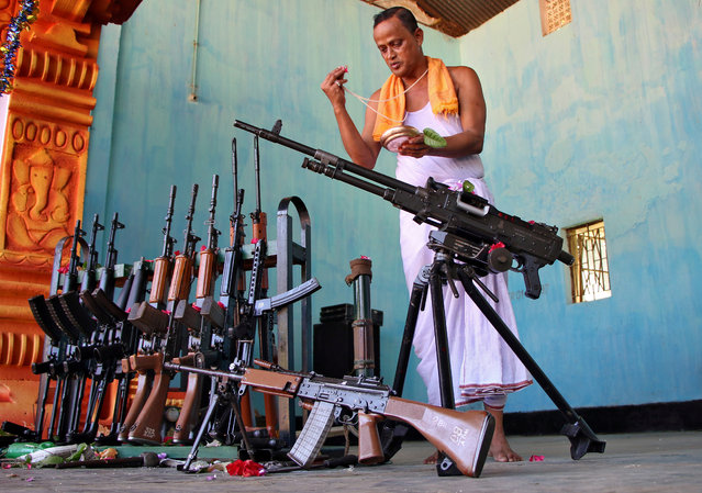 A Hindu priest worships next to weapons belonging to Tripura State Rifles during the Vishwakarma Puja or the festival of the Hindu deity of architecture and machinery in Agartala, India, September 18, 2019. (Photo by Jayanta Dey/Reuters)