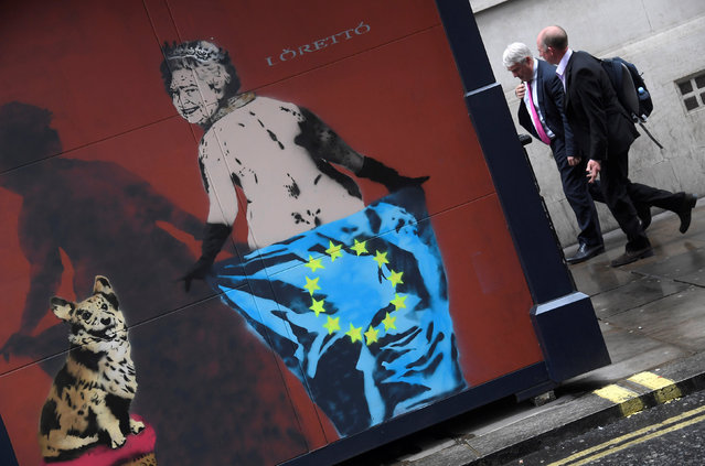 Workers walk near street art depicting Britain's Queen Elizabeth with a pet dog, holding an EU flag in London, Britain, April 24, 2017. (Photo by Toby Melville/Reuters)