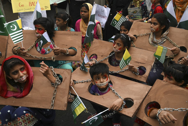 Children hold Kashmiri and Pakistani flags as they take part in an anti-Indian protest rally in Lahore on October 3, 2019. The nuclear-armed neighbours regularly target each other with mortar shells and gunfire on the de facto border known as the Line of Control (LoC) in the disputed Himalayan territory which is claimed by both India and Pakistan. (Photo by Arif Ali/AFP Photo)