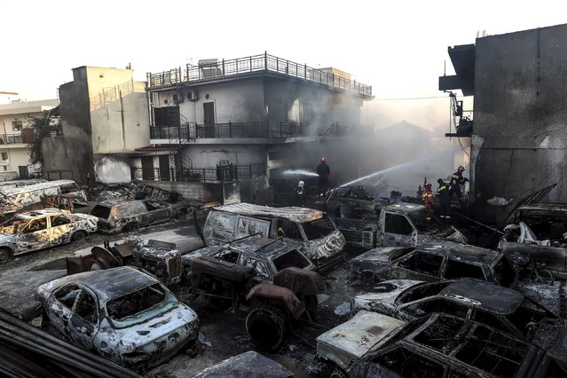 Burned cars are seen in a car lot as a wildfire rages at the town of Neapoli in the region of Laconia in Peloponnese, southern Greece July 17, 2015. Wildfires burned through rural land on the island of Evia near Athens and in the region of Laconia in the Peloponnese where one fire-fighting aircraft was forced into an emergency landing, according to the regional governor. (Photo by Vassilis Konstantopoulos/Reuters/Intimenews)