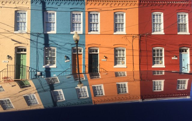 A group of colorful row houses are reflected on to the top of a black car parked on 3600 block of N street in  the Georgetown section of Washington DC, February 16, 2017. (Photo by John McDonnell/The Washington Post)