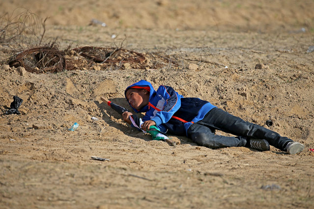 A Palestinian boy takes cover from Israeli fire during an anti-Israel protest at the Israel-Gaza border fence, in the southern Gaza Strip on November 1, 2019. (Photo by Ibraheem Abu Mustafa/Reuters)