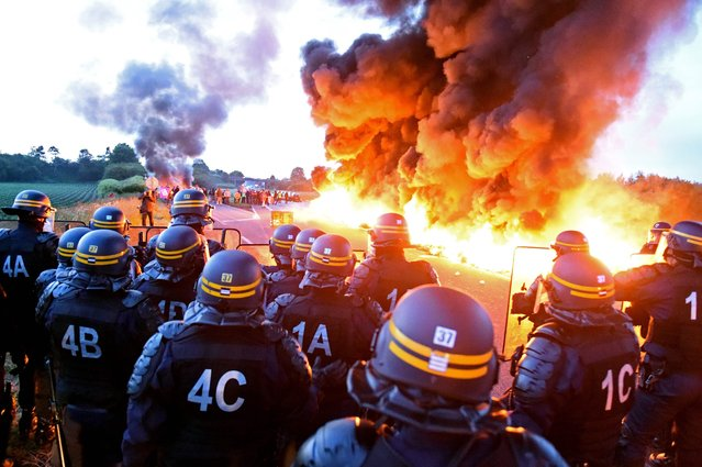 Riot police stand guard behind a fire as refinery workers hold a blockade of the oil depot of Douchy-Les-Mines to protest against the government's proposed labour reforms, on May 25, 2016. Refinery workers stepped up strikes that threaten to paralyse France weeks ahead of the Euro 2016 tournament as the government moved to break their blockades, escalating a three-month tug-of-war over labour reforms. (Photo by François L.O./AFP Photo)